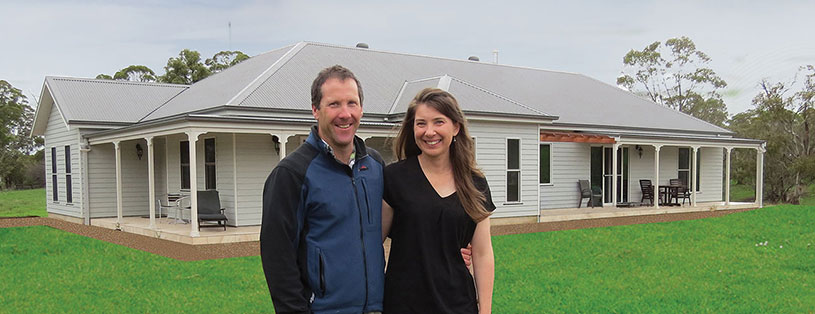 Brendan and Karen Helmrich in front of their completed home
