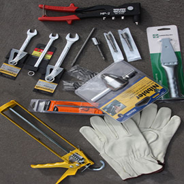 Kit home construction tools: Spanners, drill bits, philips head bits, rivet gun, scoring knife, nut setters, leather gloves. A nibbler is supplied for cutting roofing sheets on hip roofs