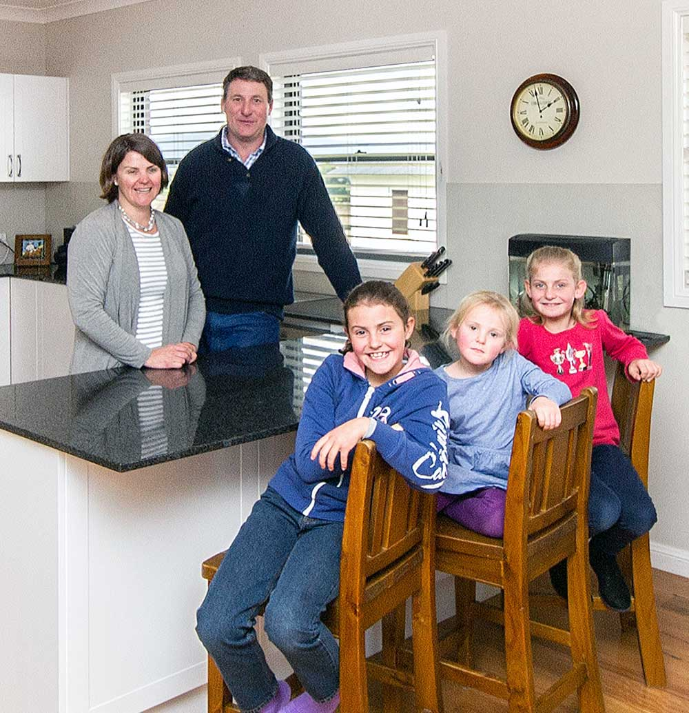 Family sitting in new kit home kitchen