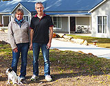 Couple with dog in front garden