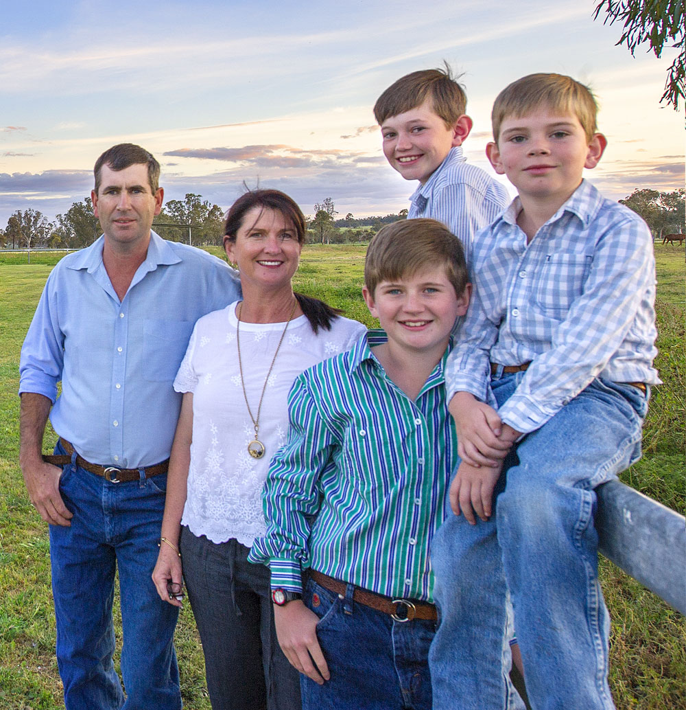 Family of 5 sitting on acreage property fence