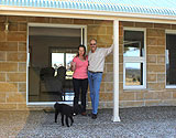 Gidleys and dog standing in doorway of new owner built home