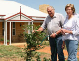 Gledhills planting tree in front of steel frame kit home
