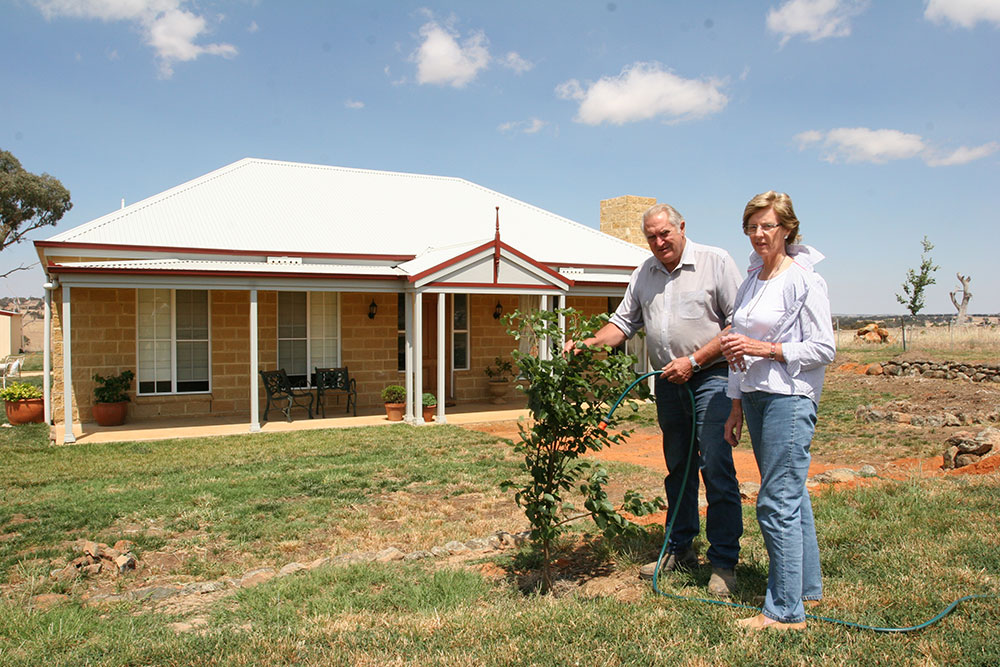 Robert and Jeanne watering new shrubs in their front garden, completed Camden in background. PAAL Kit Homes NSW VIC QLD