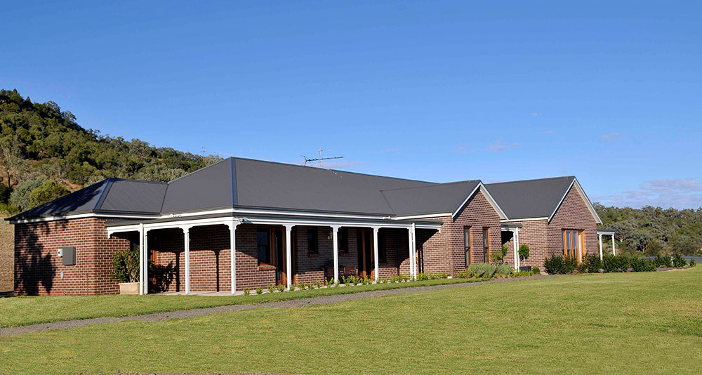 The kit home is finished in Federation Blue bricks, with a Woodland Grey iron roof and cedar windows and external doors. PAAL Kit Homes NSW VIC QLD