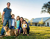 Family on lawn of property with kit home