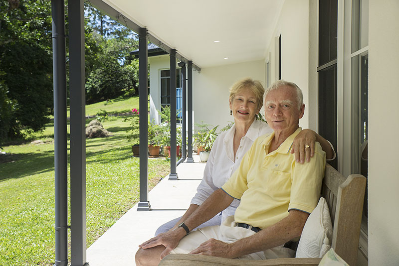 Allan & Kay sitting on the porch of their new owner built Paal Kit Home the Darling.