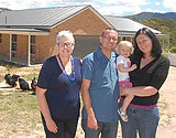 Family in front of redesigned kit home