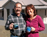 Jeff & Di outfront of new kit home with Coffee in hand